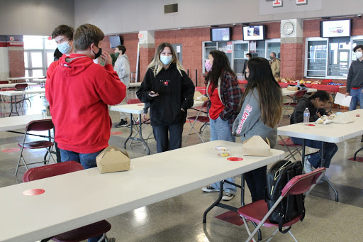 """STAND AND LAUGH: Laughing together while they chat after eating their food, freshman Nathan Evans, and juniors Justin Cassingham, Ellie Holt, Kathy Cruz, and Natalie Lopez stand in a circle. With regionals in full swing, everyone on the team needs to use the knowledge they gained from the many weeks of learning. George said that the grading system for the tests they take is not as harsh as one may think. """"At the regional level, you can often win a gold medal with a 70%. We can even win medals less than that. They"""