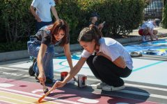 """MUSICAL INSPIRATION: Paige Buttaccio (left), a rising senior, paints her reserved parking spot that is inspired by a cassette tape. Buttaccio worked with a friend to make the spot represent both a mixtape and her love of music. """"I feel like I always listen to music at school and it gets me through stuff, so I wanted to include it in my spot,"""" Buttaccio said."""