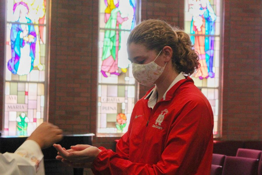 REMEMBERING AND REFLECTING: Senior Anna Campbell receives the Eucharist during the 9/11 Remembrance Mass on Friday, Sept. 10. She, like all other current high school students, was not alive on Sept. 11, 2001, but joined the MD community in gathering to remember those who lost their lives during the attack and reflect on the event through prayer.